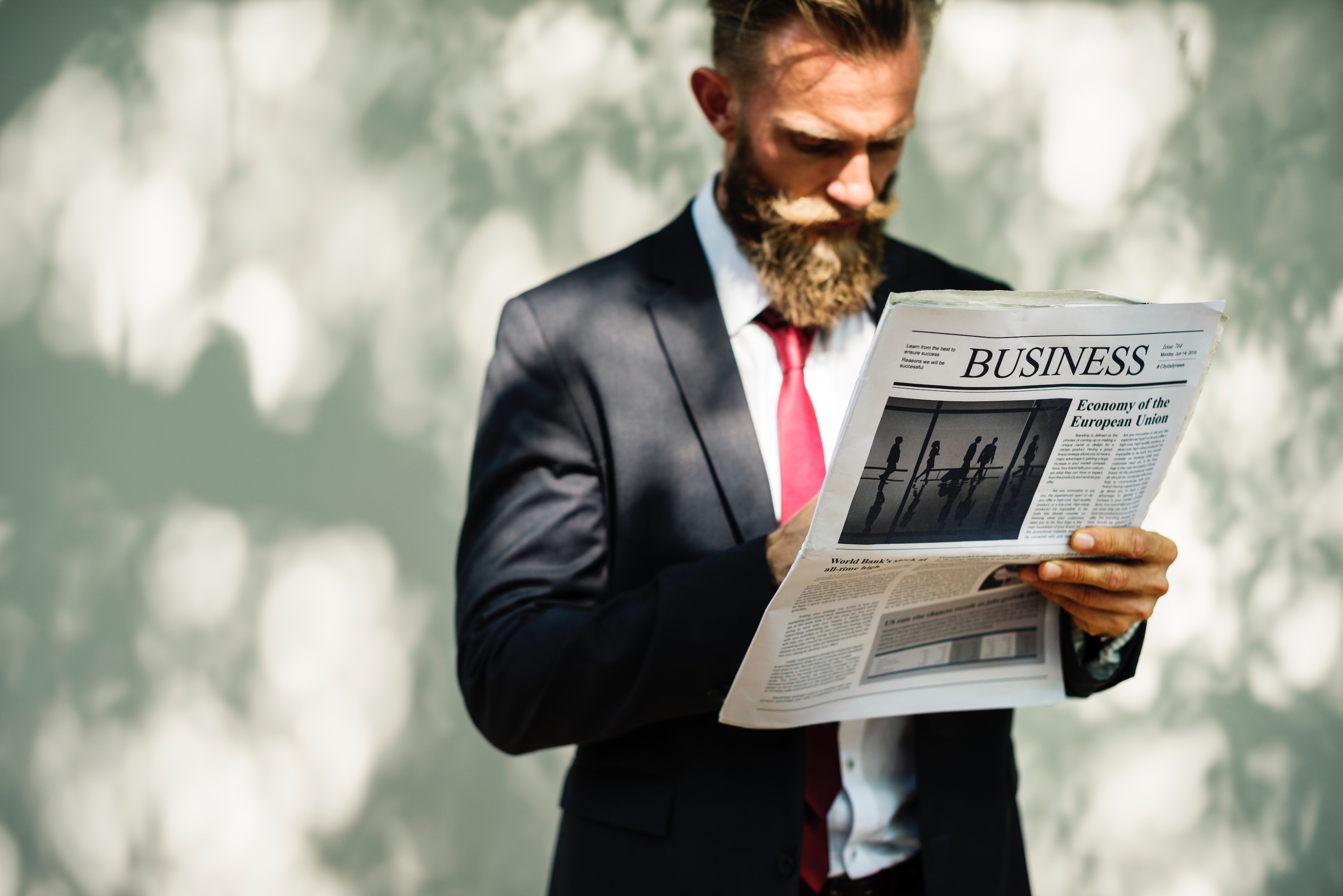posh man in suit reading business section of newspaper